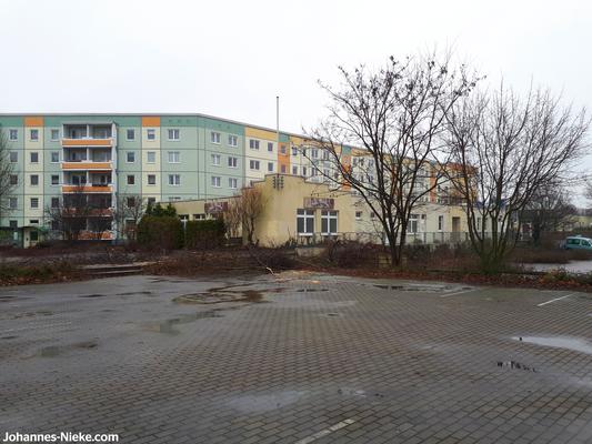 Blick von der als Marktplatz angedachten Fläche an der Adele-Sandrock-Straße zum Gebäude entlang des Fußweges A.-Kuntz-Straße 42-46 mit den Räumlichkeiten der ehemaligen Sauna im Vordergrund