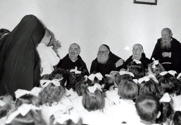 In un momento di ricreazione con alcuni bambini; accanto a loro, padre Raffaele da Sant'Elia a Pianisi (1890-1974), guardiano a San Giovanni Rotondo dal 1928 al 1941 e confessore del venerato Confratello dopo la morte di padre Agostino