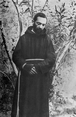 Padre Pio ritratto nel giardino del convento, qui ritratto in atteggiamento modesto, con gli occhi abbassati (agosto 1919)