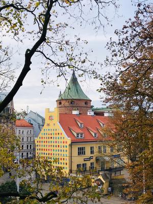 Blick vom Bastionshügel im Park auf den Pulverturm und eine Hausfassade, auf der die Insignien alle Provinzen Lettlands vereint sind.