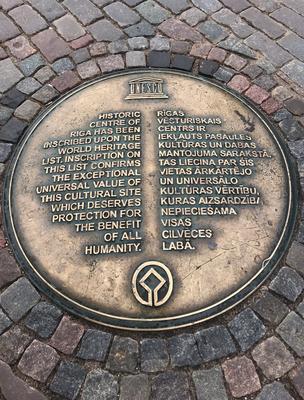 Auf dem Domplatz vor der Kirche erinnert eine in das Pflaster eingelassene Plakette an die Aufnahme Rigas in die Liste des UNESCO-Welterbes.