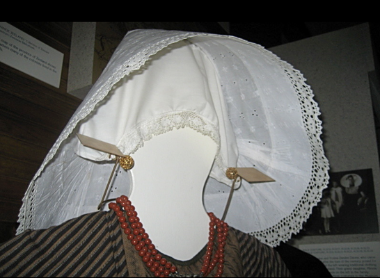 "The mannikin wears a traditional dress and her neck is adorned with a highly treasured coral bead necklace. ""Kissers"" are metal ornaments worn near the face under the caps. They were traditionally used to show marital status and family wealth."