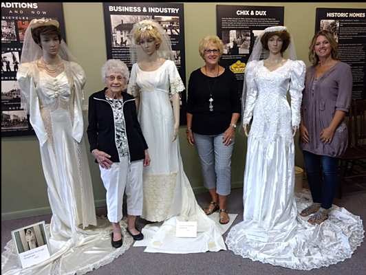 Posing with their wedding dresses are ninety-nine year old Genevieve (DeJongh) Huizenga, her daughter Elaine (Huizenga) Matthysse, and granddaughter Lisa (Matthysse) Flipse (photo by Arlene - August 8, 2018) - USED WITH PERMISSION