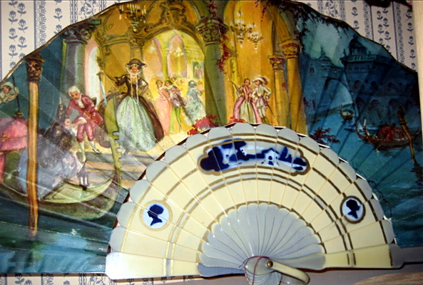 This lady's fan is a gold design of Victorian ladies and men and a turquoise design of a gondola on water. The reverse side is a landscape of rocks, water and homes.