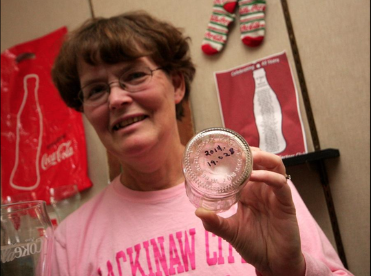 Kathy Westveld holds a bottle that is displayed in the Zeeland Historical Society's storefront with the date that it was donated by the Westveld's to the organization. Rob Wetterholt Jr./Sentinel Staff
