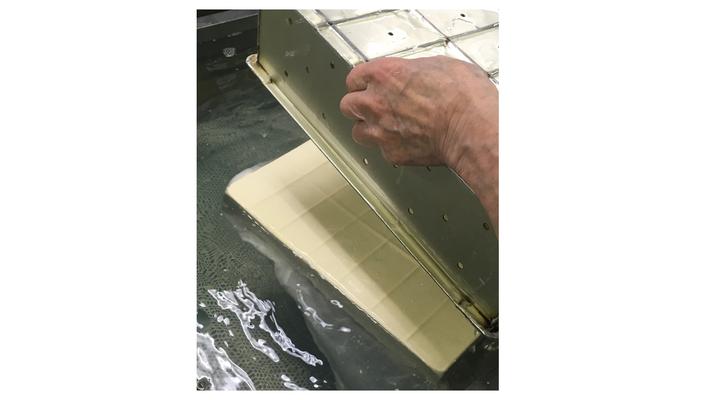 豆腐を水槽の中で型枠から外します。