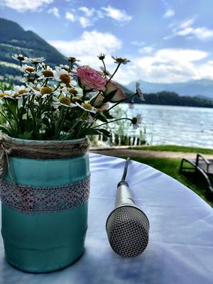 Alma Cilurzo Hochzeitssängerin Hochzeitslocation Schlosshotel Merlischachen Trauung am See Mirkophon Detailaufnahme Blumen