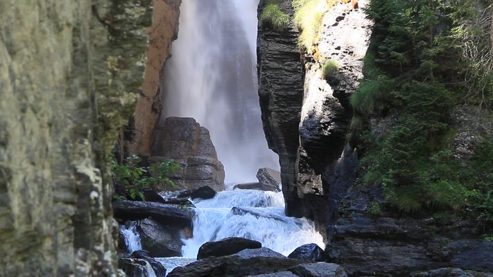 Wasserfall gut versteckt zwischen zwei Bergwänden.