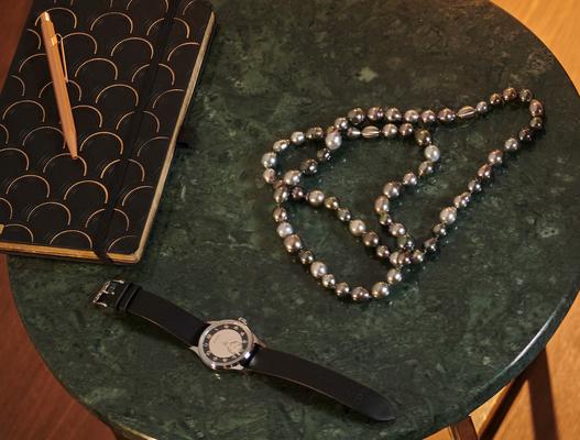 Auch daliegend anziehend: Perlenkette von «Gellner» und Uhr «Heritage Classic Tuxedo» von «Longines».