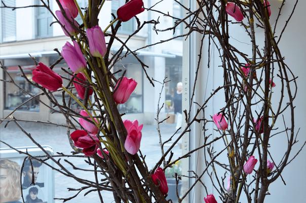 """Frühlingsarrangement mit Blumen im Schaufenster des Friseursalons """"CUT!- Der Frisör"""" in Winnenden."""