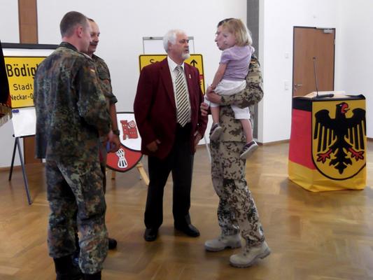 Während des Empfangs: Oberstleutnant Dietzman (links), Oberfeldwebel d.R. Markus Gessler (links, hinten), Oberstleutnat d.R. Gerd Teßmer (Mitte) und Oberstleutnant Wilke mit seiner Tochter auf dem Arm bei einer angeregten Unterhaltung. (Bild: R. Weiß)