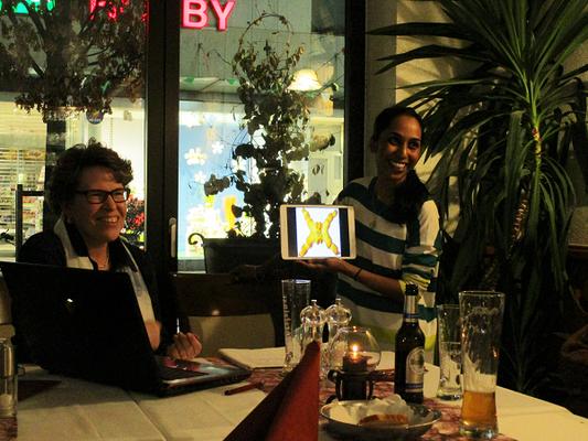 """DIG-Vorsitzende Rita Schneider-Cartocci (l.) und Jincy Zappaterra (r.) erklären Besonderheiten von Ferrara: wie das Brot """"coppia"""", dessen Bild gezeigt wird."""