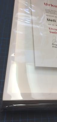 Schlichte Einrahmung der Urkunde. Holzrahmen aus dem Emmental weiss lasiert. Entspiegeltes Bilderglas. Distanzleisten aus Museumskarton auf Mass angefertigt. Auszeichnung erhöht aufgelegt. Alterungsbeständige reversible fixierung.