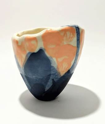 "This unique yunomi is handmade in ""Jasmin"" earthenware using the ""pinching"" technique. The native colour of the material is a gentle creamy white. The yunomi is coloured with cobalt blue/black copper oxide underglaze and soft orange underglaze."