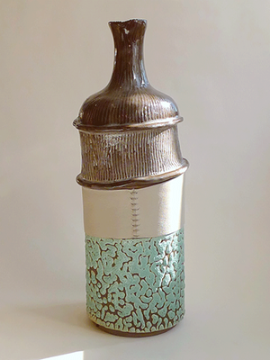 This unique hand built bottle/soliflore is made in dark brown earthenware by Solargil (France). The decorations are in reclaimed and hand sewn leather (grey), white underglaze, turquoise glazing and transparent glazing. It is perfectly watertight.