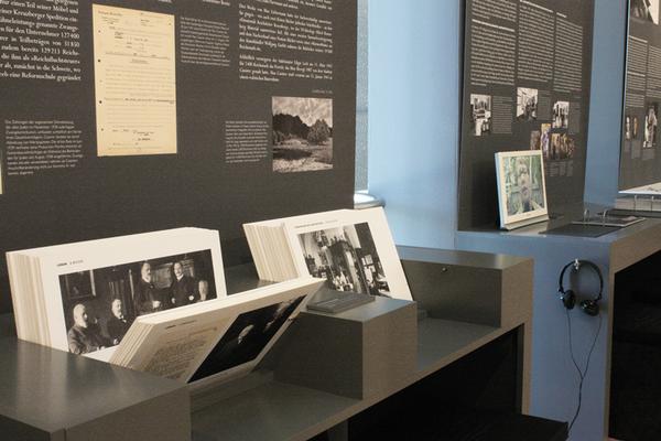 """Tisch mit Reproduktionen von Dokumenten und Fotos zum Thema """"Enteignung, Vertreibung und Verwertung: Das Beispiel Max Cassirer""""."""