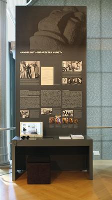 """Banner und Tisch zum Thema """"Handel mit Entarteter Kunst"""". Der im Tisch integrierte Bildschirm zeigt einen Film und Dokumente zum Thema."""