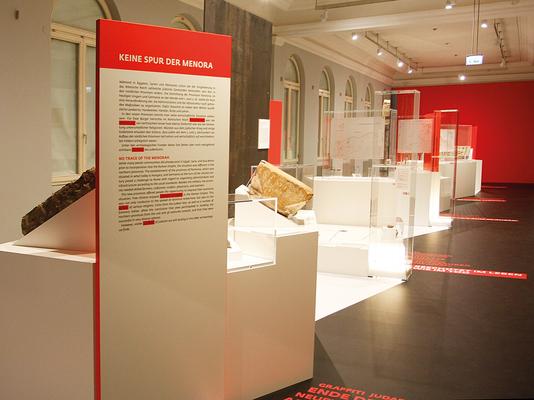 """Im Hauptraum der Ausstellung wird jedes Thema auf einer eigenen """"Insel"""" dargestellt. Originalobjekte, Grafiken und erläuternde Texte bebildern den jeweiligen Sachverhalt. Auf dem Fußboden sind die Ausstellungsstationen durch ein weiße  Linie verbunden."""