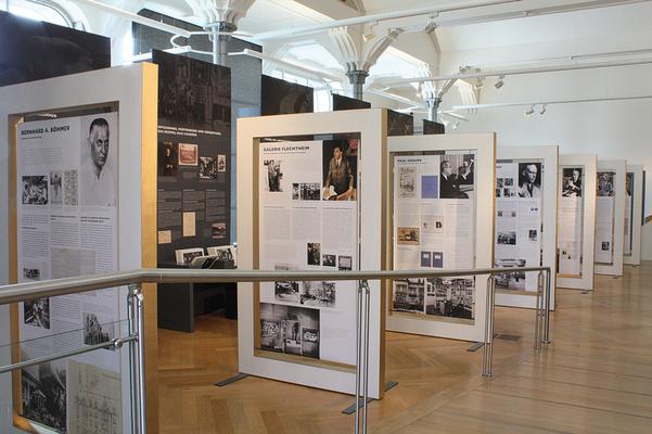 In den übergroßen Bilderrahmen sind vierzehn Kunsthändler und ihre Rolle im Nationalsozialismus dargestellt.