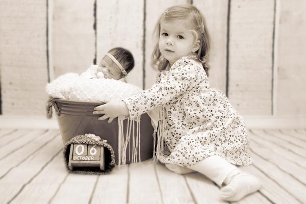 Newbornfotoshooting, Baby im Eimer mit Schwester, Hausen