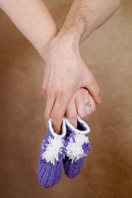 Schwangerschaft Fotoshooting, kleine Schuhe in den Händen der Eltern