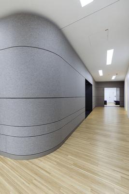 Freie Formgebung und geschwungene Raumteiler ergeben ein ansprechende Innengestaltung dieser Arztpraxis