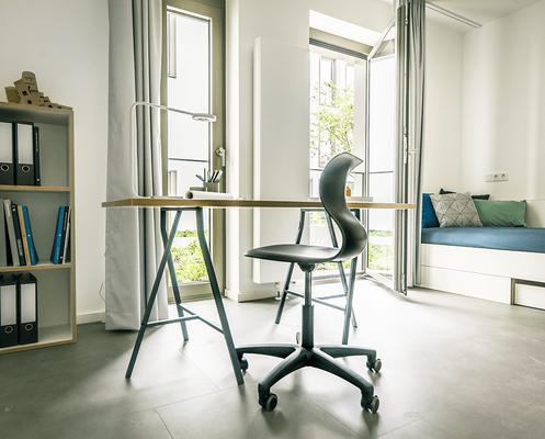 Schreibtisch und Regal dürfen bei der Ausstattung der Zimmer des Studentenwohnheims nicht fehlen