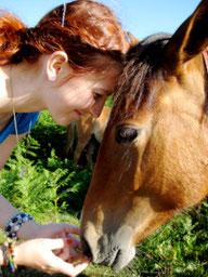 Natascha Leiler und ein Pferd stehen sich Kopf an Kopf gegenüber