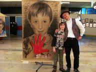 Der Künstler Tomé mit Markus vor dessen rote Hand Porträt