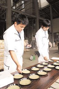米の品質などを確認する山根指導員(左)と大嵩丈夢指導員(右)=25日午前、JAおきなわ八重山地区営農振興センターライスセンター