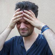 Mann fasst sich an den Kopf. Schmerzen im Kiefergelenk und Migräne