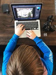 Suse Eckart sitzt am Laptop. Neben ihr liegen eine Festplatte, eine Kmaera und eine SD-Karte.