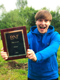 Suse Eckart hält freudig strahlend den Film-Award von BNI hoch.