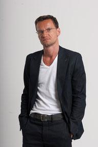 Manfred Bruckner mit weißem Shirt und dunklem Sakko.