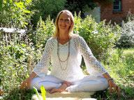 Angel-Coach Carola Gaubatz im Grünen mit hellen Orbs im Hintergrund