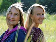 Die Energie-Coaches Aurelia und Carola auf einer Wiese im Wald mit blauem Orb im Hintergrund