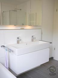 weißer Badunterschrank mit Schubladen, Wandhängender Waschtischunterschrank in weiß Hochglanz mit umlaufender, weißer Griffleiste & zwei Schubladen, Waschbeckenunterschrank für Doppel-Aufsatzbecken, Waschbeckenunterschrank auf Gehrung, Griffleiste