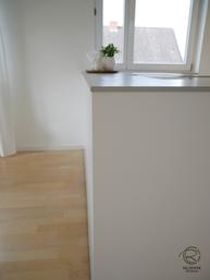 Grifflose Fronten bei Kochinsel, grifflose, weiße Design Küche mit oriongrauen Schubladen von Blum Legrabox mit Halbkochinsel 12 mm Keramik Arbeitsplatte