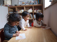 イスに座って絵を描く三人の子ども