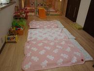 布団を敷いている、ピンクと白の毛布