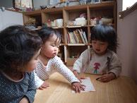 テーブルで話す、三人の子ども