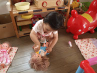 お人形にミルクをあげている子ども