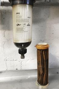 Eingesetzter neuer Wasserfilter und alter, verbrauchter Filter