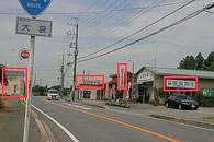 右側に「産直館」「ひより食堂」「自動精米所」という看板、左側に新築の家屋が見えたらあと100mです