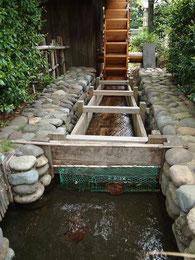 民家の裏に回ると水車のある用水路が
