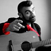 Le Baron de Vezeline avec sa guitare pour l'éloge des Artistes présenté par M'Zlle Anna