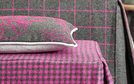 Ein Kissen und zwei Tischdecken, alles grau und pink gemustert