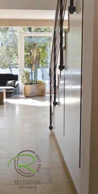 weiß lackierter Schrank nach Maß unter Treppe mit flächenbündigen, massiven Eichgriffleisten