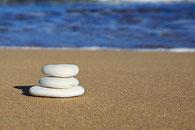 Steine gestapelt am Strand, auf Sand, am Meer