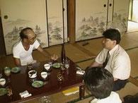 写真( H12・8)は、杜氏:宿里時吉(笠沙町)を訪ねて、焼酎造りを伺う若かりし頃の藤本一喜氏。